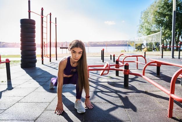 Mulher bonita atleta fazendo exercícios matinais no playground da rua. treinamento ao ar livre. treino feminino