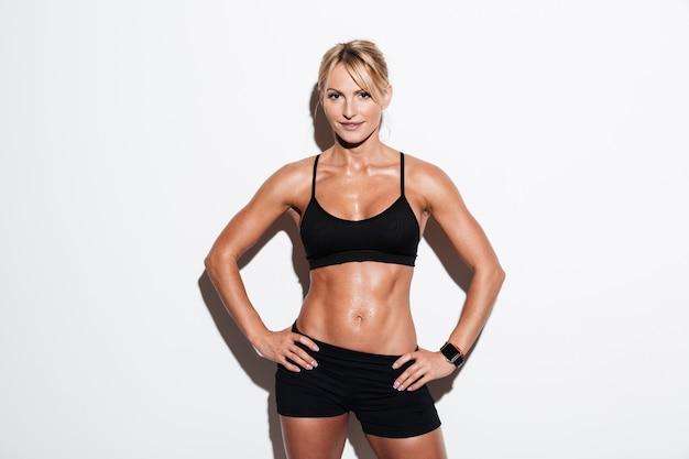 Mulher bonita atleta sorridente posando em pé