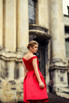 Mulher bonita atraente em um vestido vermelho em pé perto do edifício histórico com colunas