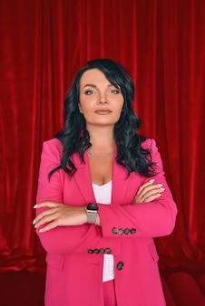 Mulher bonita atriz na moda em um terno rosa sobre fundo de cortinas de veludo vermelho