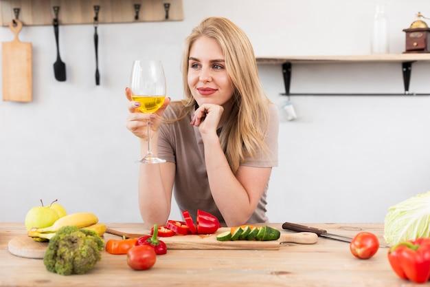 Mulher bonita, bebendo e comendo legumes