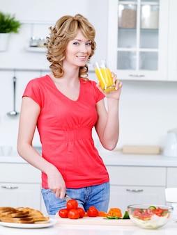 Mulher bonita bebendo suco de laranja e cozinhando na cozinha - dentro de casa
