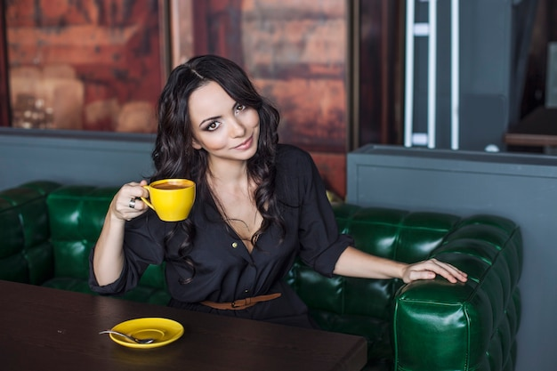 Mulher bonita bebendo uma bebida quente. modelo alegre e feliz com uma xícara de café brilhante