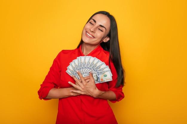 Mulher bonita bem-sucedida animada e feliz se divertindo com muito dinheiro enquanto posa no fundo da parede amarela