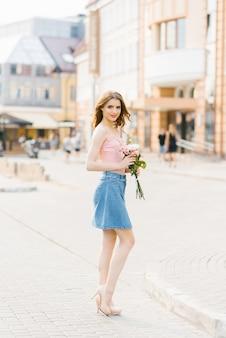 Mulher bonita bonita com maquiagem profissional em um top rosa e saia jeans em uma cidade de verão, segurando um buquê de rosas brancas e rosa
