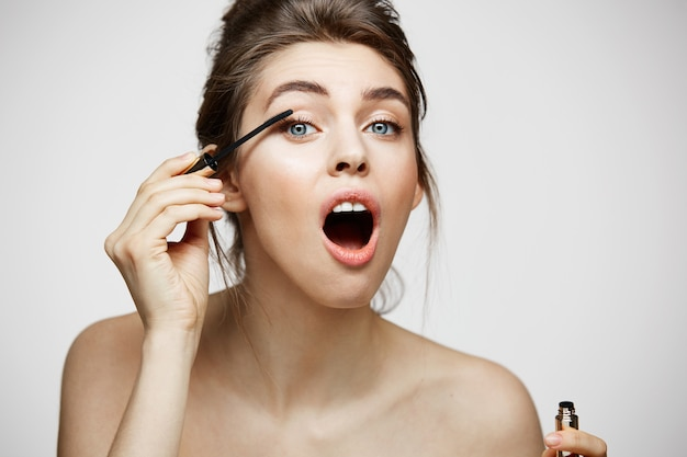Mulher bonita bonito tingir os cílios com a boca aberta. conceito de saúde e cosmetologia de beleza.