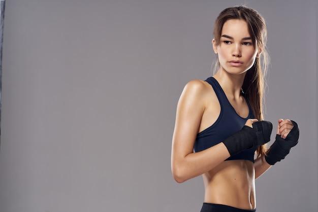 Mulher bonita boxe exercícios exercícios fitness posando com fundo escuro