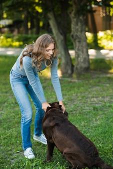 Mulher bonita brincando com seu cachorro no parque