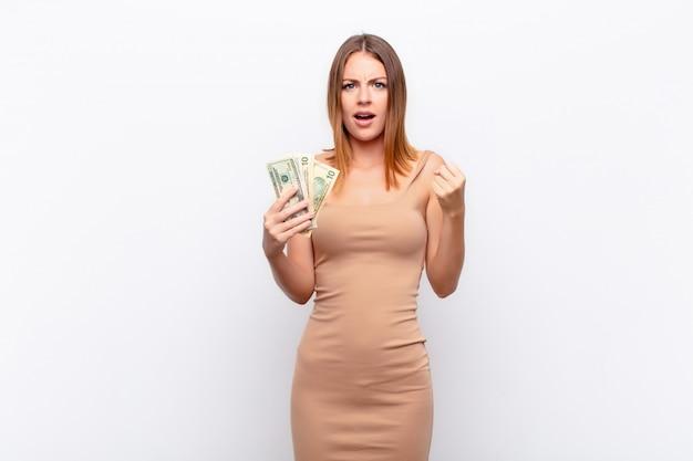 Mulher bonita cabeça vermelha gritando agressivamente com uma expressão de raiva ou com os punhos cerrados comemorando sucesso com notas de dólar