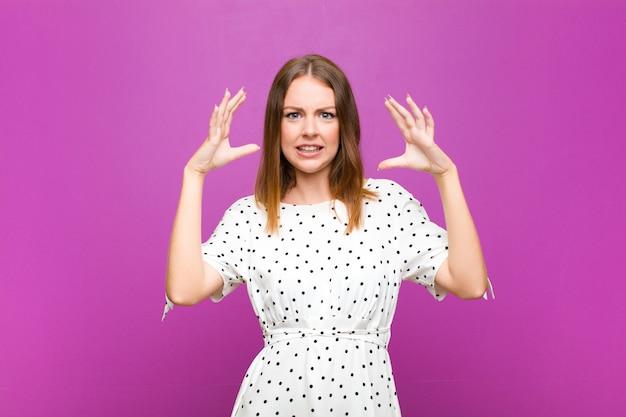 Mulher bonita cabeça vermelha gritando com as mãos no ar, sentindo-se furioso, frustrado, estressado e chateado contra a parede roxa