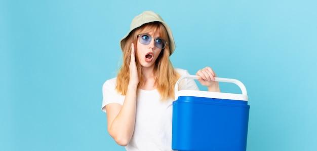 Mulher bonita cabeça vermelha se sentindo feliz, animada e surpresa e segurando uma geladeira portátil. conceito de verão