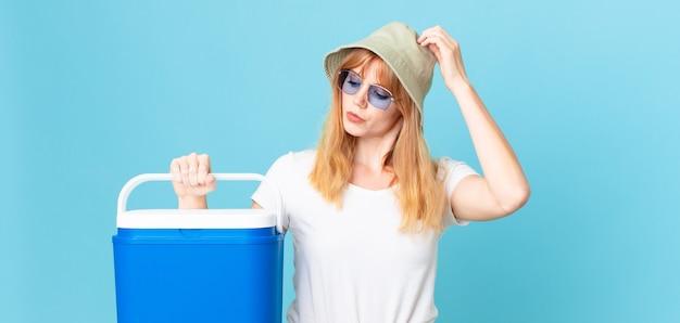Mulher bonita cabeça vermelha se sentindo perplexa e confusa, coçando a cabeça e segurando uma geladeira portátil. conceito de verão
