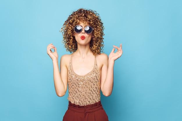 Mulher bonita cabelo cacheado lábios vermelhos mãos perto do rosto aparência atraente modelo azul parede isolada
