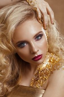 Mulher bonita, cabelos loiros, maquiagem profissional, cor dourada.