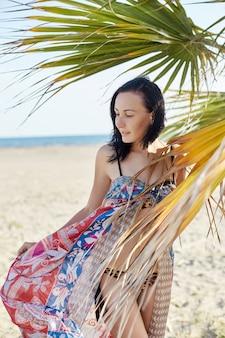 Mulher bonita caminha ao longo da praia em dia de sol.