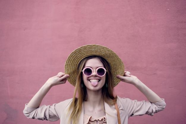 Mulher bonita caminhada ao ar livre moda verão parede rosa viagem pela cidade