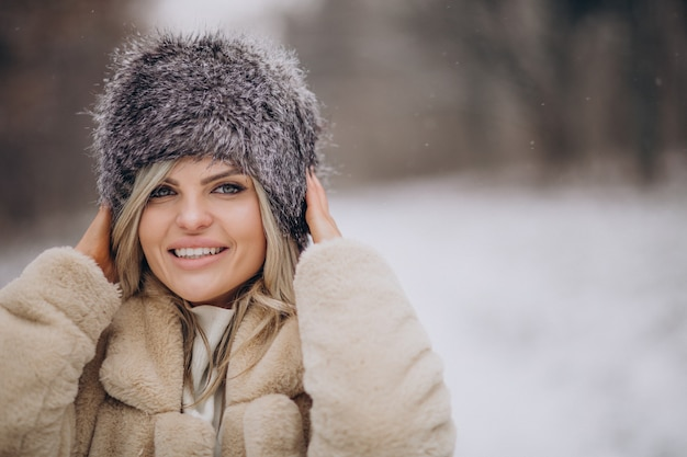 Mulher bonita caminhando em um parque cheio de neve