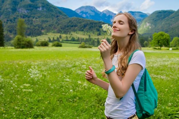 Mulher bonita caminhando nos prados alpinos e cheirando uma flor fresca