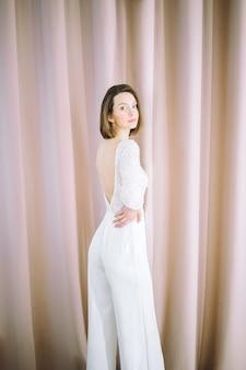Mulher bonita camisa branca e calça de pé e olhando no quarto com pérola