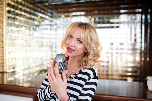 Mulher bonita canta com um microfone