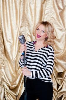 Mulher bonita cantando com microfone retrô