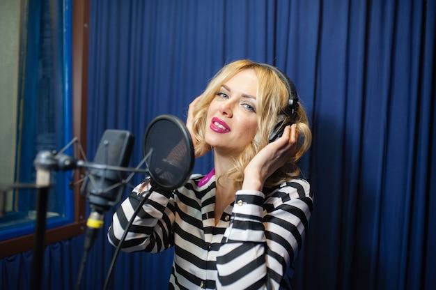 Mulher bonita cantando em um estúdio de gravação