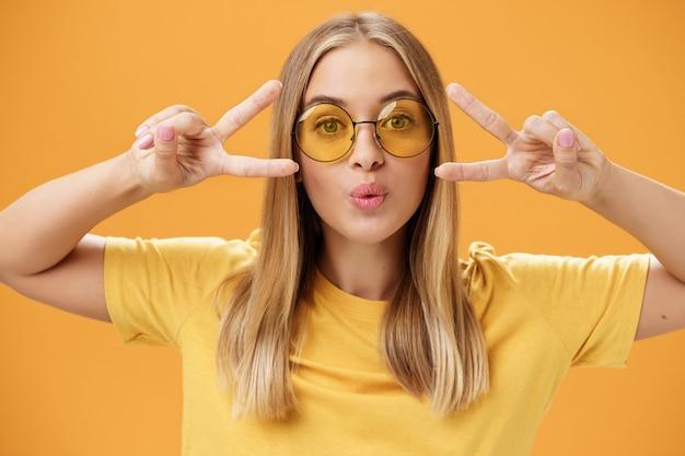Mulher bonita carismática despreocupada em óculos de sol redondos da moda e t-shirt dobrando os lábios em um beijo, mostrando sinais de paz ou discoteca perto de olhos dançando se divertindo na festa contra um fundo laranja. estilo de vida.