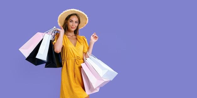 Mulher bonita carrega roupas novas, enquanto segura pacotes coloridos com fundo roxo, grandes promoções