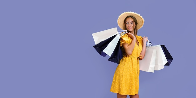Mulher bonita carrega roupas novas, enquanto segura pacotes coloridos com grandes promoções de cores de fundo