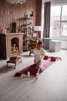 Mulher bonita caucasiana com cabelo loiro em roupas brancas, sentada no tapete de ioga com os olhos fechados e relaxando