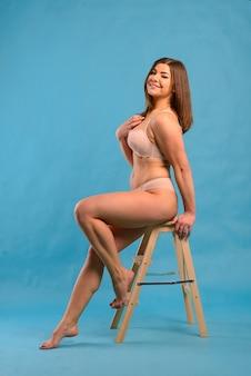 Mulher bonita caucasiana com corpo plus size usando calcinha de renda rosa em um fundo azul do estúdio