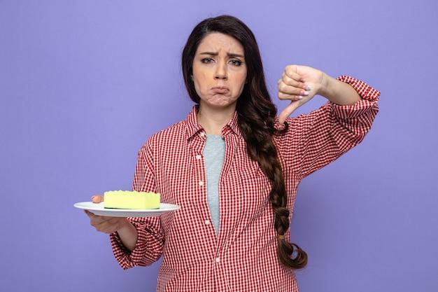 Mulher bonita caucasiana de limpeza triste segurando uma esponja no prato e apontando para baixo