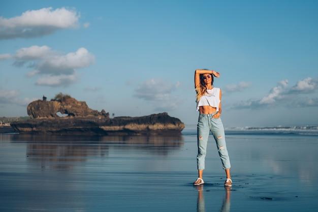 Mulher bonita caucasiana em forma de blusa branca e calça jeans refletindo a praia junto ao oceano à luz do sol