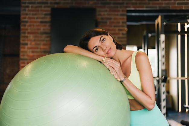 Mulher bonita caucasiana em forma de roupa esportiva adequada na academia com fitball