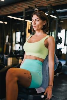 Mulher bonita caucasiana em forma de roupa esportiva adequada para ginástica na máquina de perna malhando