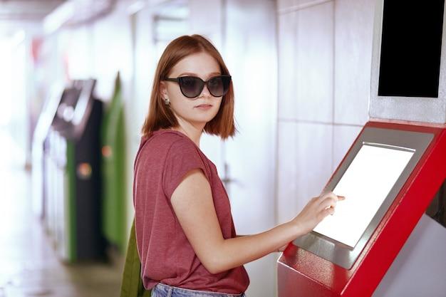Mulher bonita caucasiana em óculos de sol da moda, coloca perto de caixa eletrônico com tela em branco, precisa retirar dinheiro