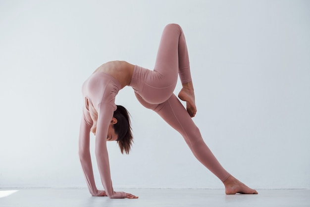 Mulher bonita caucasiana fazendo exercícios contra um fundo branco