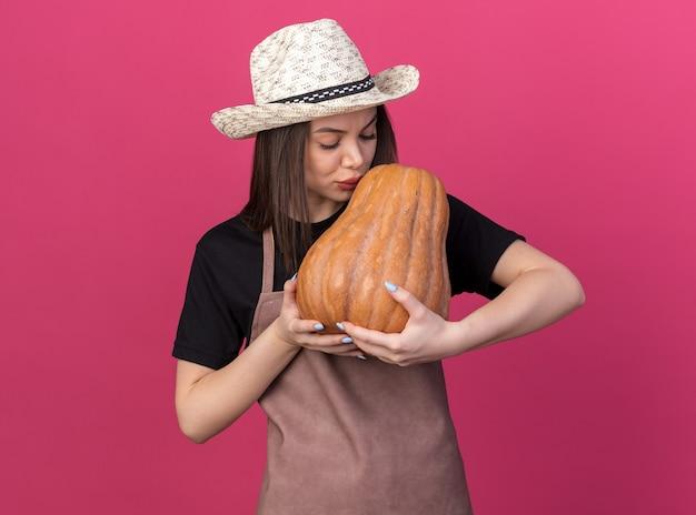 Mulher bonita caucasiana jardineira satisfeita com um chapéu de jardinagem segurando e beijando uma abóbora
