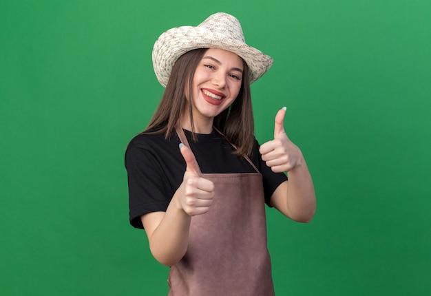 Mulher bonita caucasiana jardineira sorridente com chapéu de jardinagem levantando duas mãos isoladas na parede verde com espaço de cópia