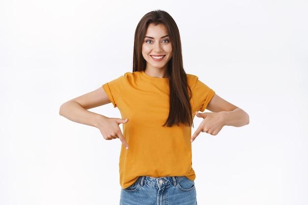 Mulher bonita caucasiana morena confiante e atrevida em uma camiseta amarela, dê uma olhada no link legal e participe do evento, apontando o dedo para baixo, olhe para a câmera e assertivo, fundo branco