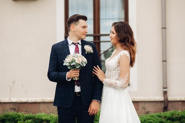 Mulher bonita caucasiana posa para a câmera com seu marido bonito com cabelo preto curto e terno preto