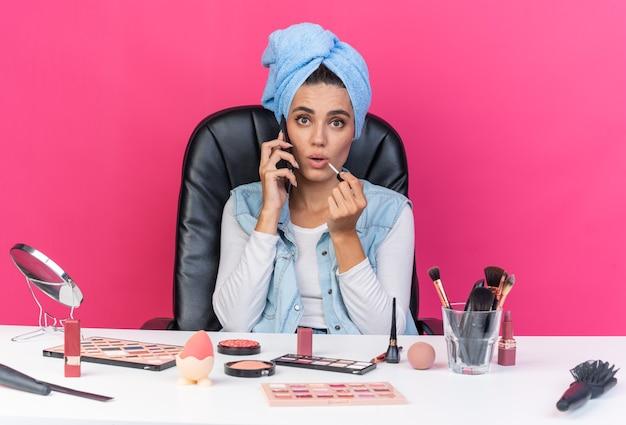 Mulher bonita caucasiana surpresa com o cabelo enrolado em uma toalha, sentada à mesa com ferramentas de maquiagem, falando no telefone e segurando brilho labial