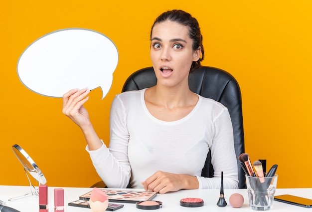 Mulher bonita caucasiana surpresa, sentada à mesa com ferramentas de maquiagem segurando um balão de fala