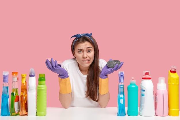 Mulher bonita chateada morde lábios em desgosto, segura esfregões, parece estressada, faz tarefas domésticas, limpa a poeira, usa spray