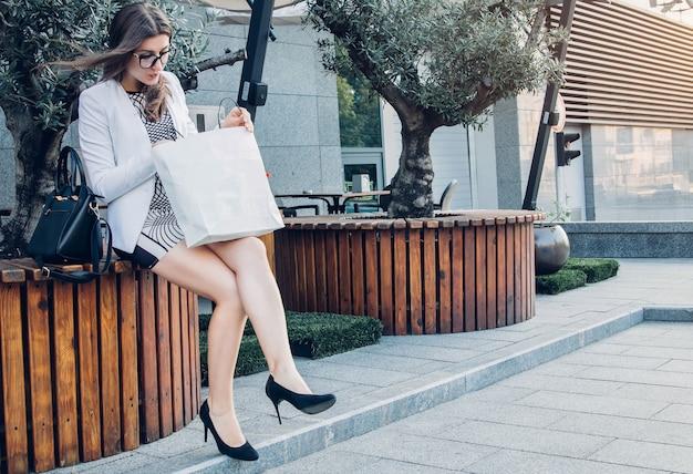 Mulher bonita checando coisas novas na embalagem depois das compras