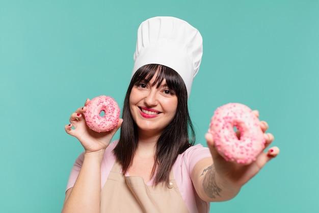 Mulher bonita chef com uma expressão feliz e rosquinhas segurando