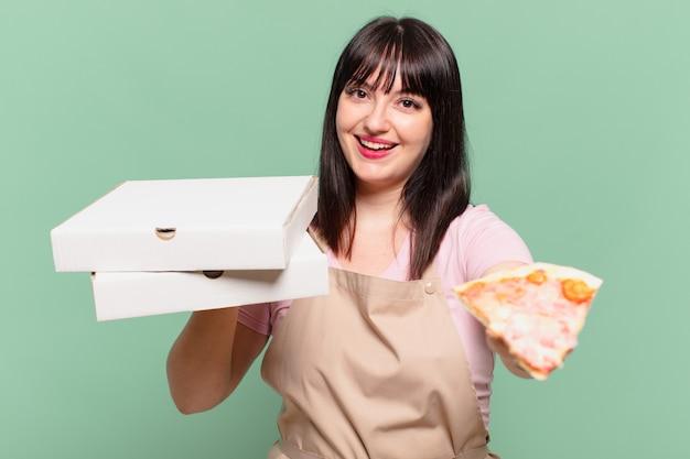 Mulher bonita chef com uma expressão feliz e segurando uma pizza
