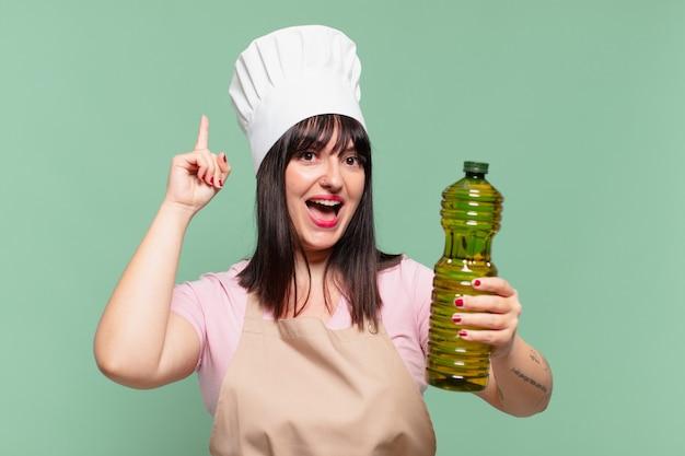 Mulher bonita chef comemorando uma vitória bem-sucedida e segurando uma garrafa de azeite de oliva