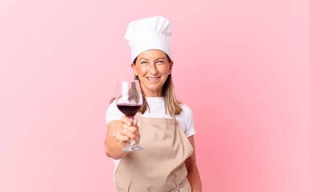 Mulher bonita chef de meia-idade com uma taça de vinho