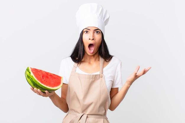 Mulher bonita chef hispânica espantada, chocada e atônita com uma surpresa incrível e segurando uma melancia